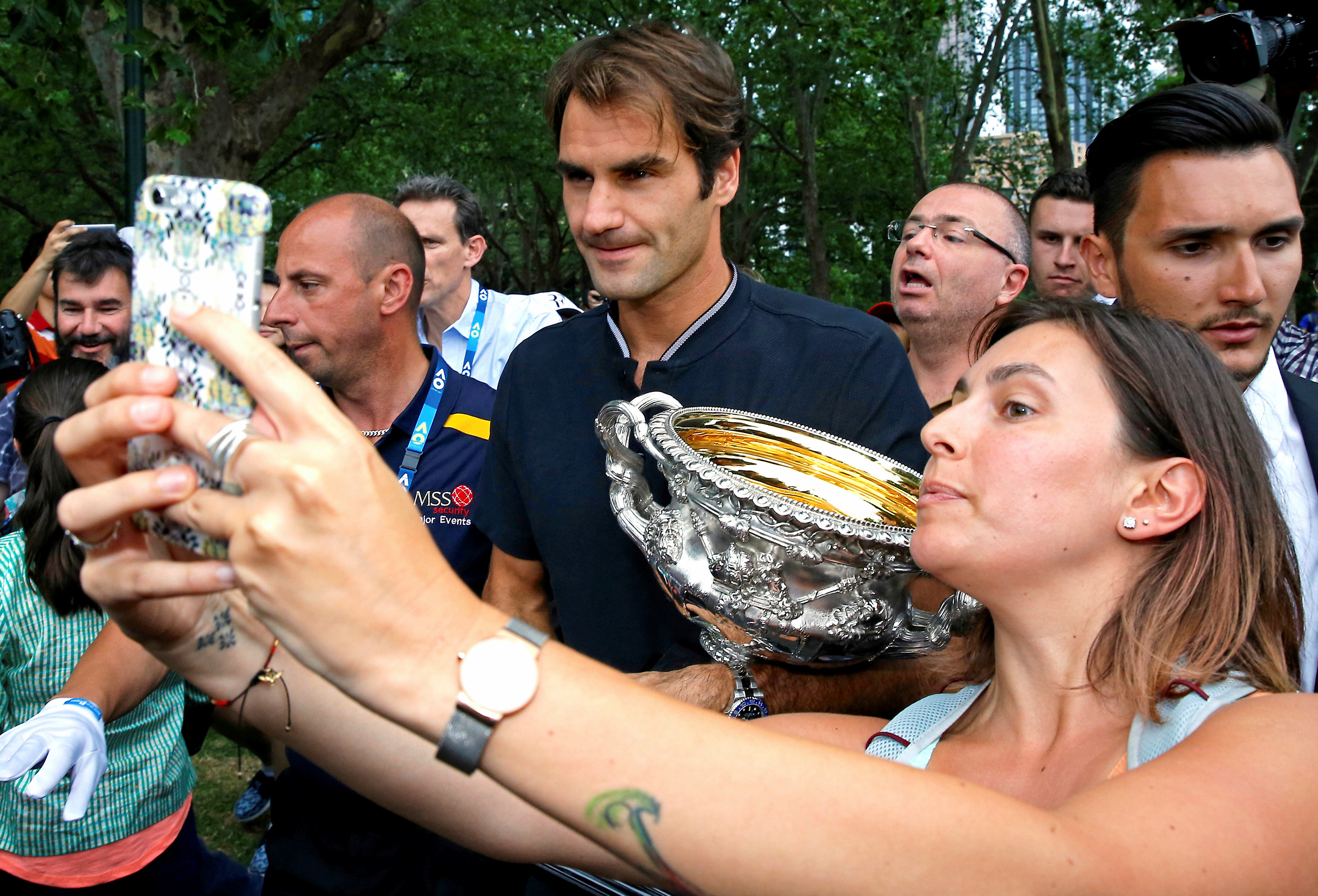 A woman takes a selfie with Switzerland's Roger Federer as he holds the trophy during a photo call the morning after he won the Men's singles final at the Australian Open tennis tournament in Melbourne, Australia, January 30, 2017. REUTERS/Issei Kato
