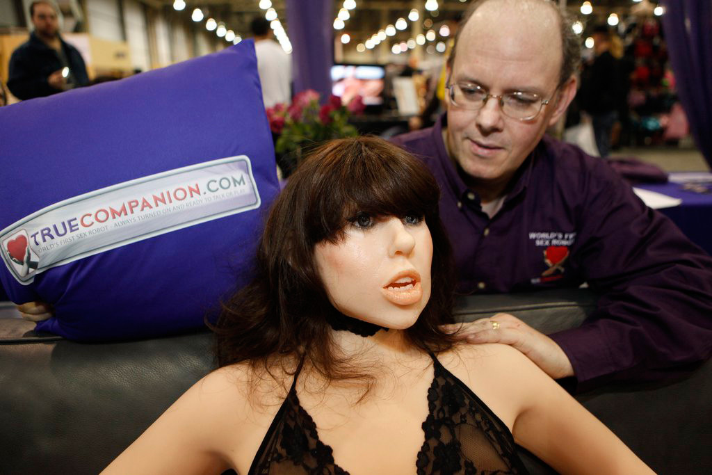 Douglas Hines, founder of True Companion, poses with a life-size rubber doll named Roxxxy during the Adult Entertainment Expo