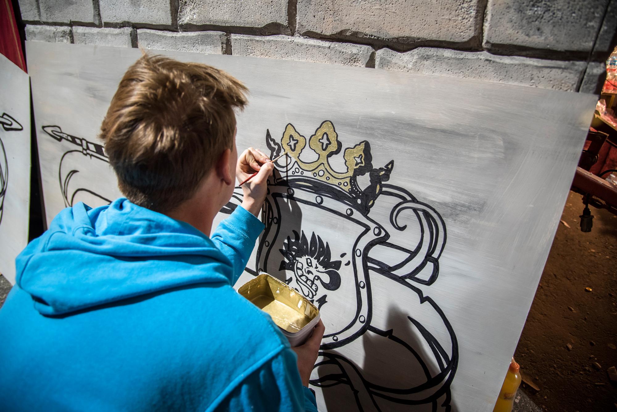 Fabian ist der Künstler der Truppe. Hier malt er an der Verkleidung des Traktors, der die Burg am Cortège ziehen wird.