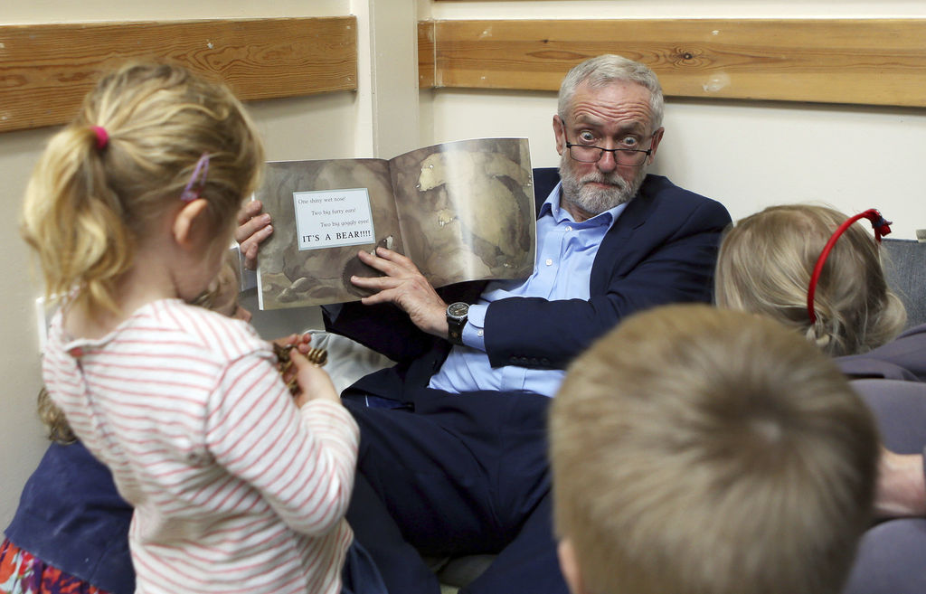 Britain's Labour Party leader Jeremy Corbyn reads with children as he visits Brentry Children Centre in Bristol, western England during Labour's election campaign Friday April 21, 2017. Britain will hold a general election on June 8. (Steve Parsons/PA via AP)
