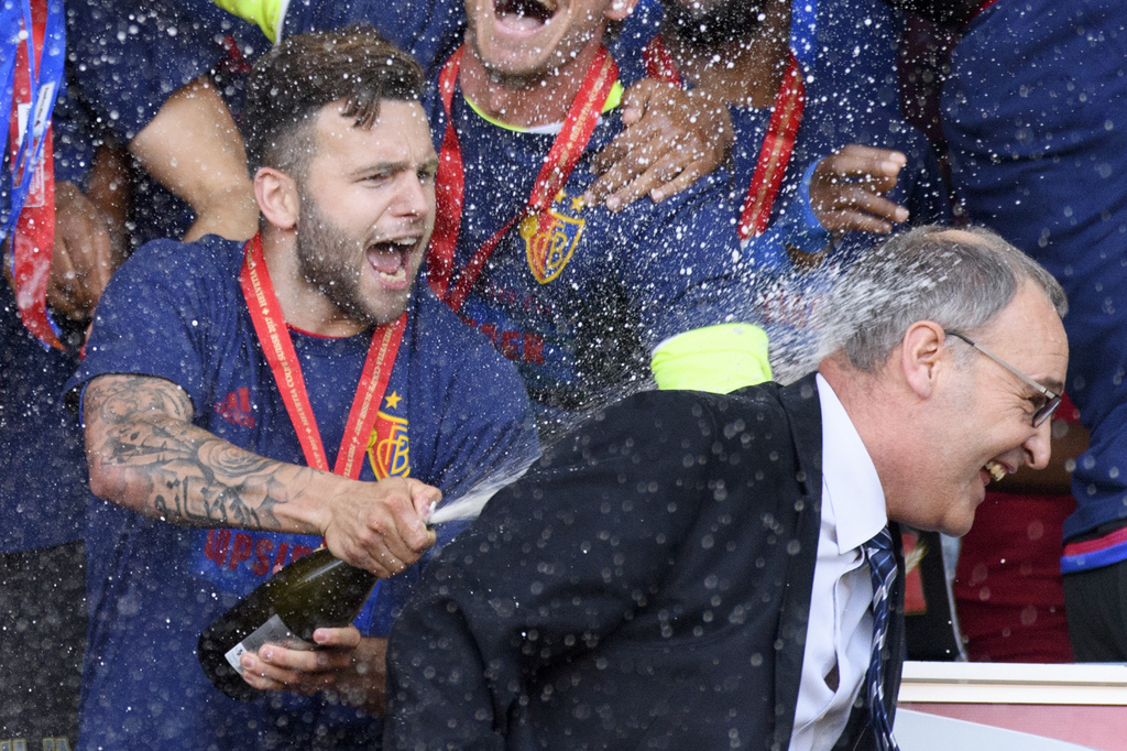 Basel's midfielder Renato Steffen, left, sprays with champagne Federal councillor Guy Parmelin, right, as Basel's players celebrate with the trophy after winning the the Swiss Cup final soccer match between FC Basel 1893 and FC Sion at the stade de Geneve stadium, in Geneva, Switzerland, Thursday, May 25, 2017. (KEYSTONE/Laurent Gillieron)