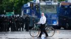 A man walks in front of riot police during the protests at the G20 summit in Hamburg, Germany, July 7, 2017. REUTERS/Hannibal