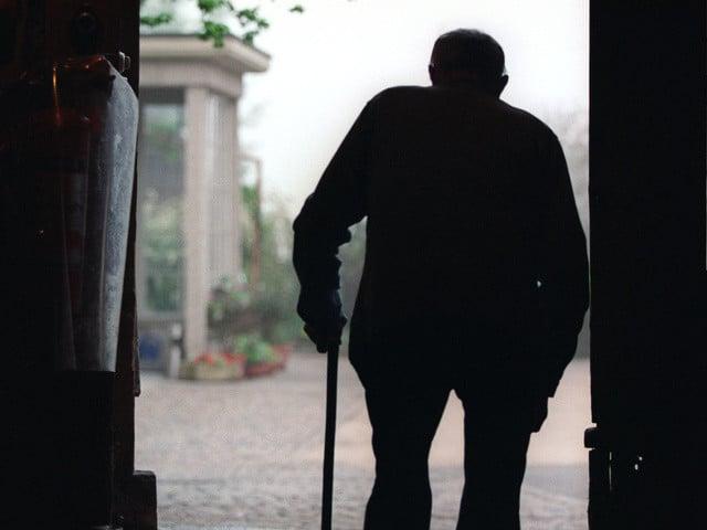 Ein Pensionaer, der im Dienstbotenheim Oeschberg in Koppigen, Bern, lebt, geht aus dem Stall in Richtung Haus, aufgenommen am