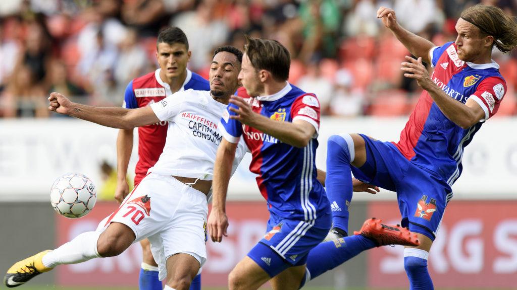 Le joueur valaisan Matheus Cunha, gauche, lutte pour le ballon avec le milieu balois Luca Zuffi, centre, et le defenseur balo