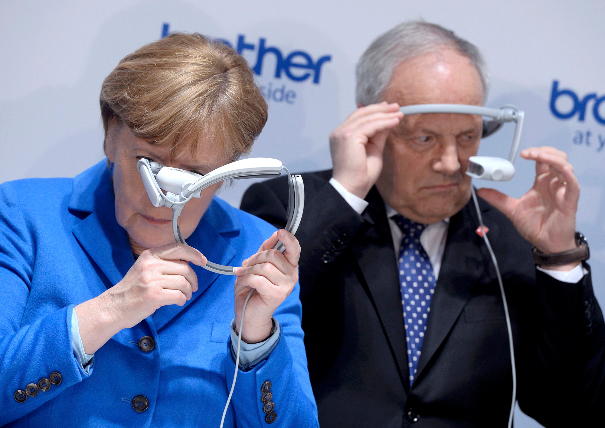 German Chancellor Angela Merkel and Swiss President Johann Schneider-Ammann (R) look at head-mounted display units on the Bro