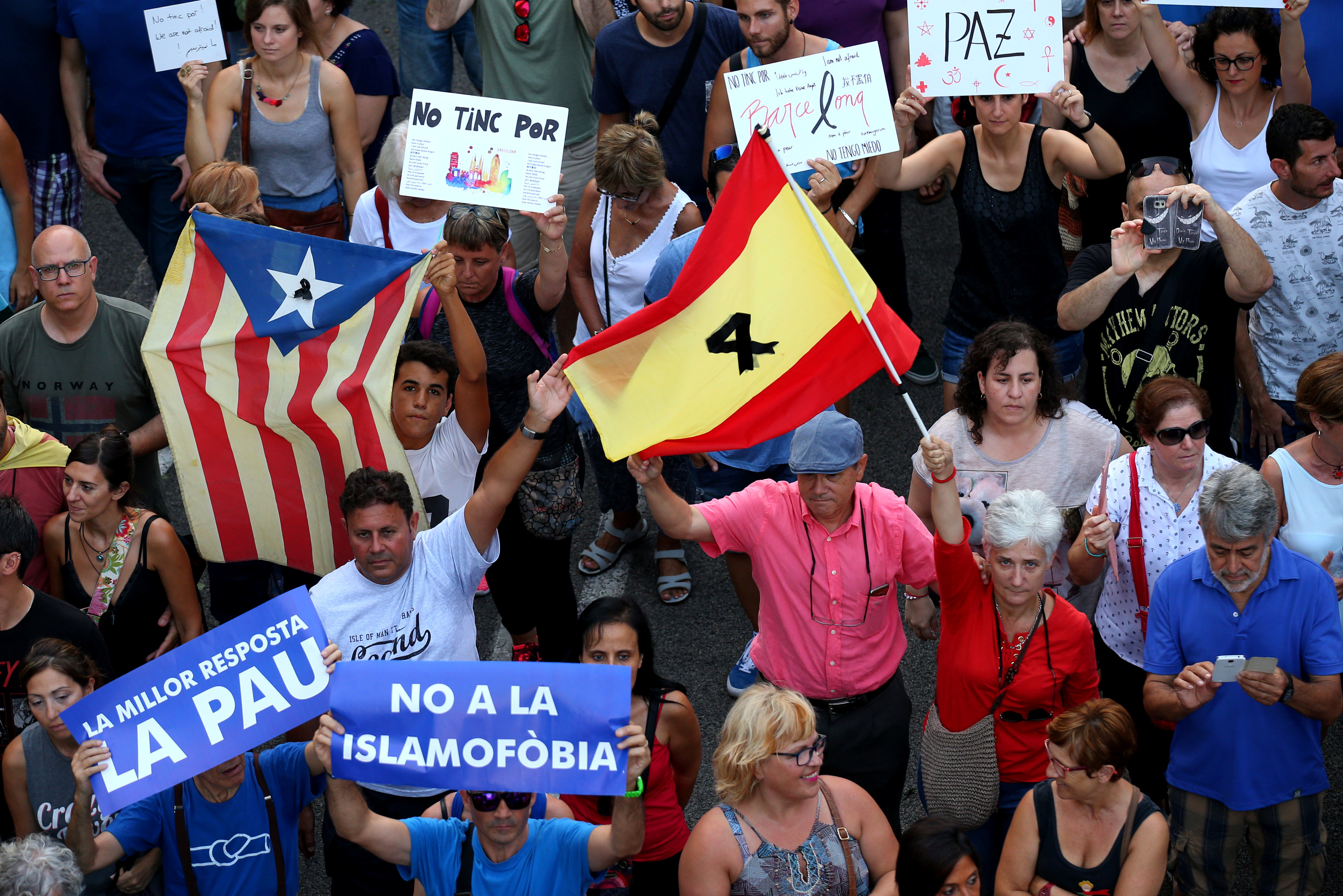 People hold signs and flags during a march of unity after the attacks last week, in Barcelona, Spain, August 26, 2017. REUTER