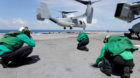 Crewmen brace themselves from the propeller wash of a Marine Corps MV-22B Osprey departing the aboard the USS Kearsarge as U.