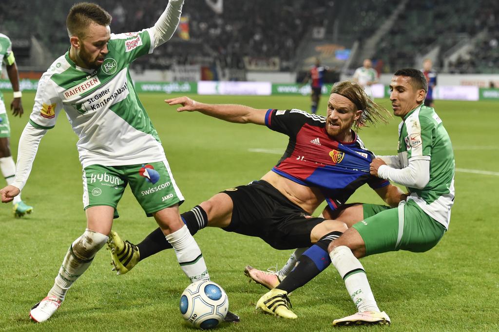 Basels Michael Lang, Mitte, geht gegen die St. Galler Andreas Wittwer, links, und Yanis Tafer zu Boden, im Fussball Super Lea