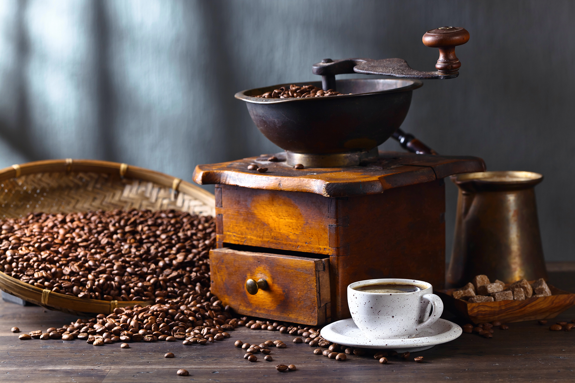 Cup of black coffee , coffee grinder and roasted beans on wooden table