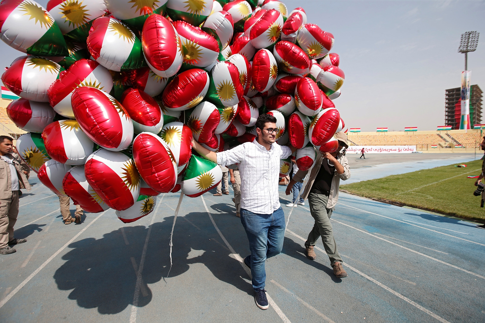 A man carries balloons decorated with Kurdistan flags before the start of a rally calling to vote yes in the coming referendu