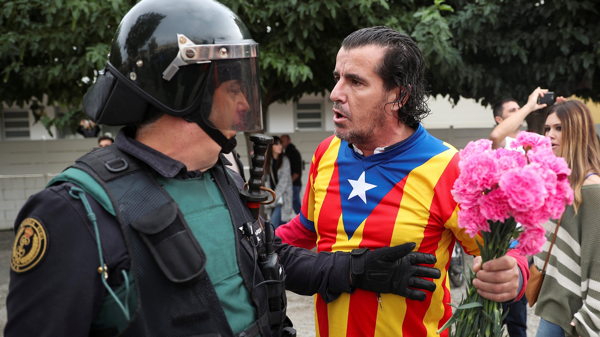 A man wearing a shirt with an Estelada (Catalan separatist flag) and holding carnations faces off with a Spanish Civil Guard
