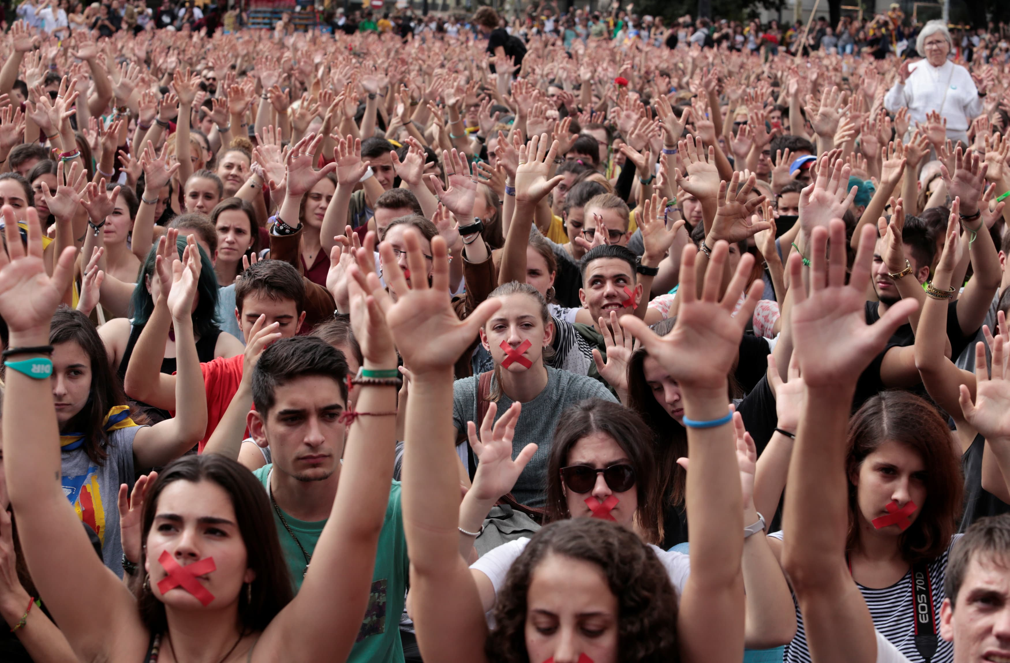 People raise their hands during a protest the day after the banned independence referendum in Barcelona, Spain October 2, 201