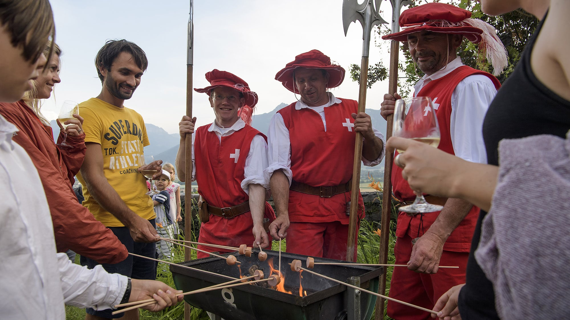 Des personnes font griller des cervelas sur un feu lors de la Fete national suisse ce mardi 1 aout 2017 a Yvorne. (KEYSTONE/J