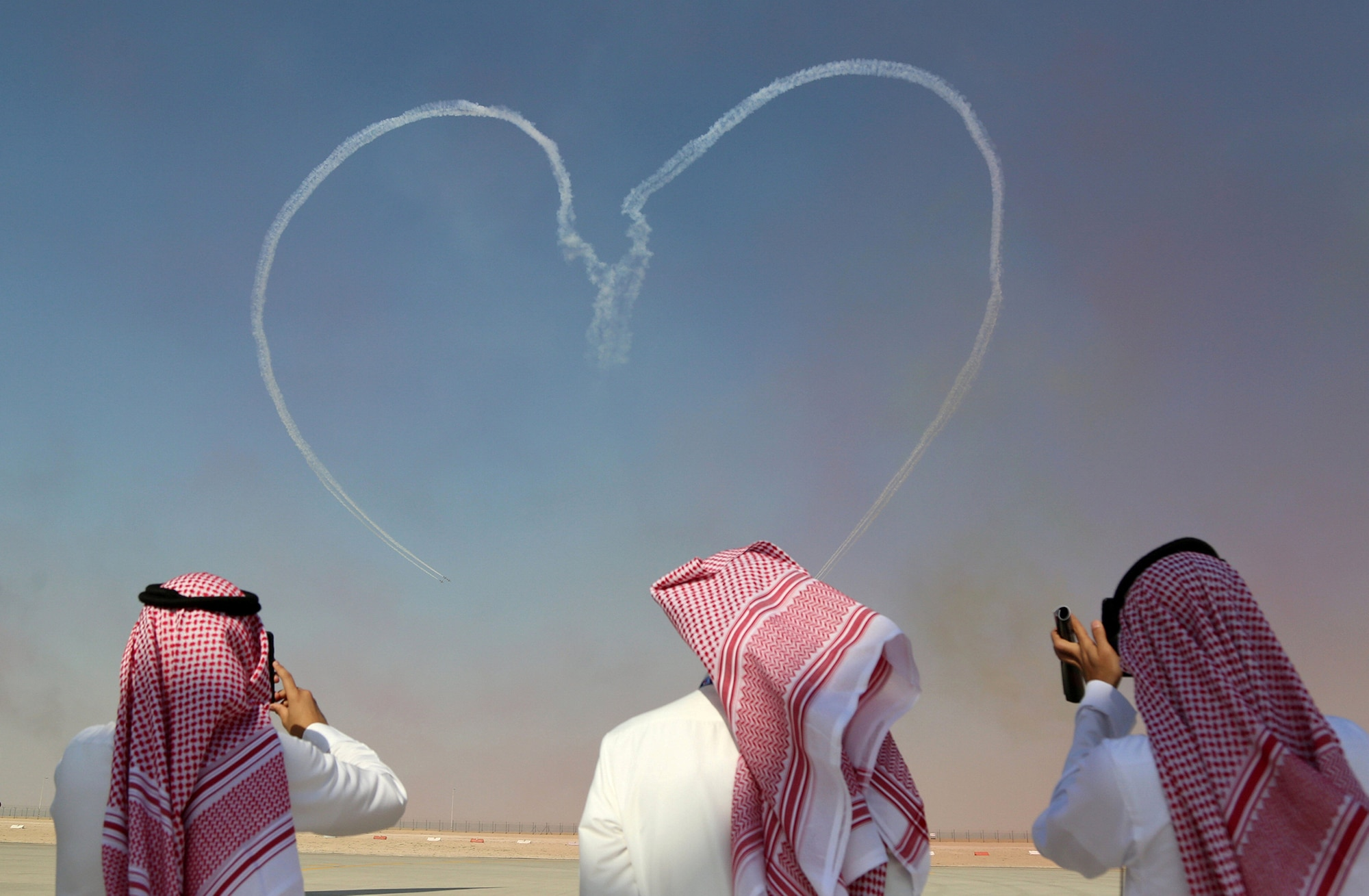 Visitors take pictures as Al Fursan aerobatic team of the United Arab Emirates Air Force performs during the Dubai Airshow in