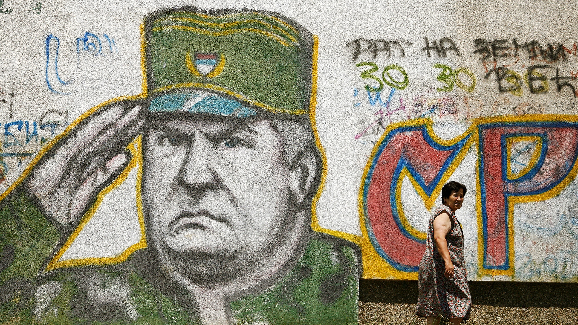 FILE PHOTO: A woman walks past a mural of Bosnian Serb wartime general Ratko Mladic in Belgrade, Serbia June 11, 2009. REUTER