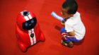 A child holding an entrance ticket watches a smart self-learning robot during the World Robot Conference at the Yichuang Inte