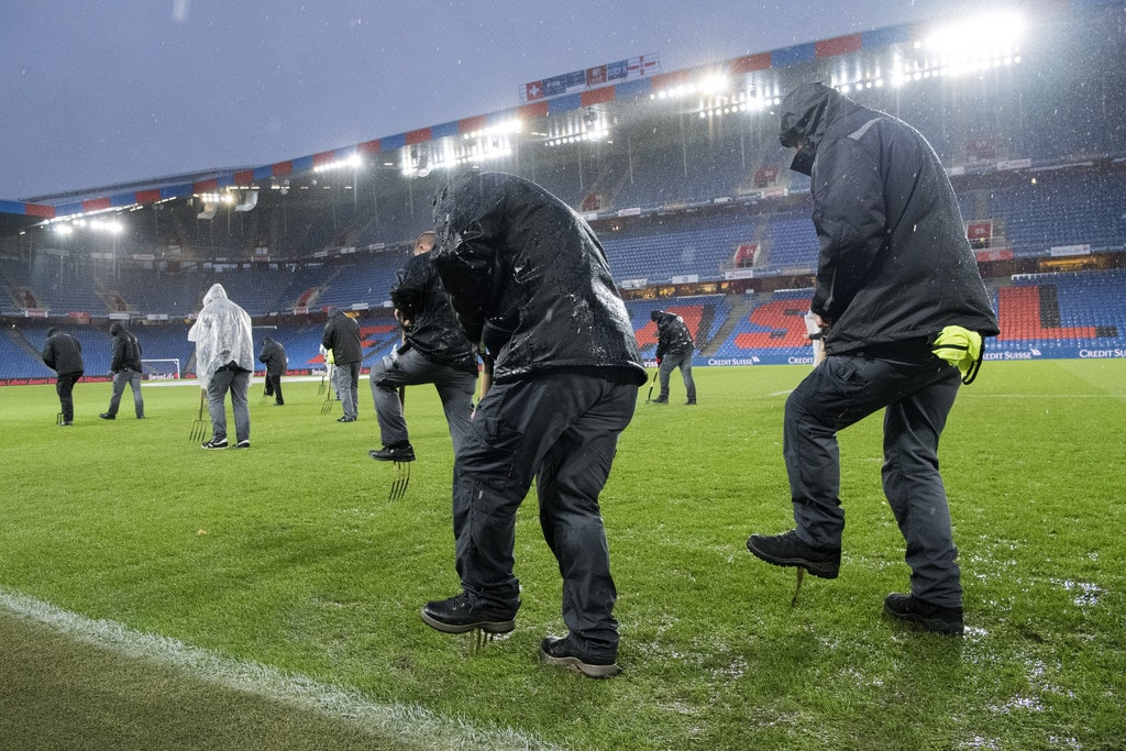 Staff members work under heavy rain to evacuate water from the field, prior the 2018 Fifa World Cup play-offs second leg socc
