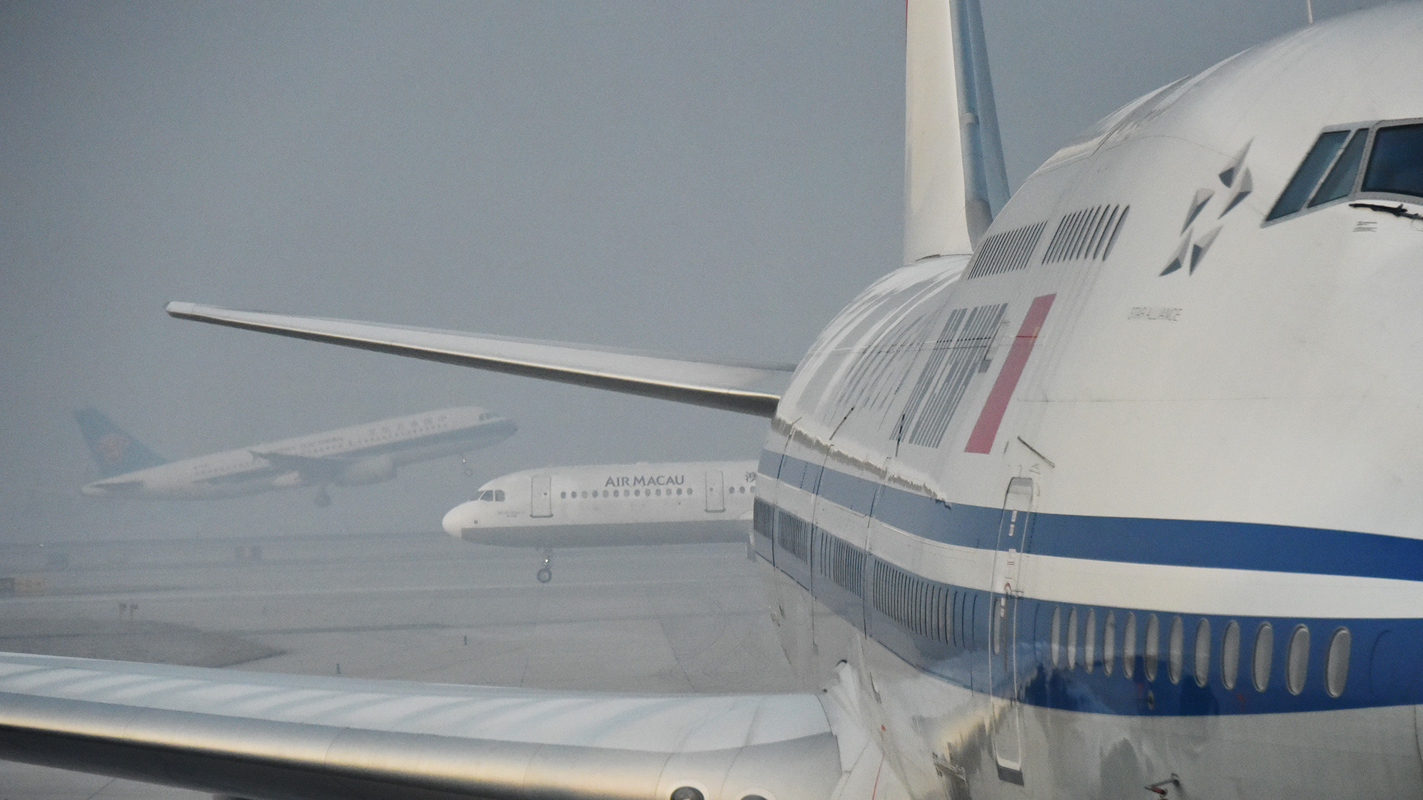 BEIJING, CHINA - DECEMBER 23:  (CHINA OUT) Planes sit at Beijing International Airport in heavy smog on December 23, 2015 in