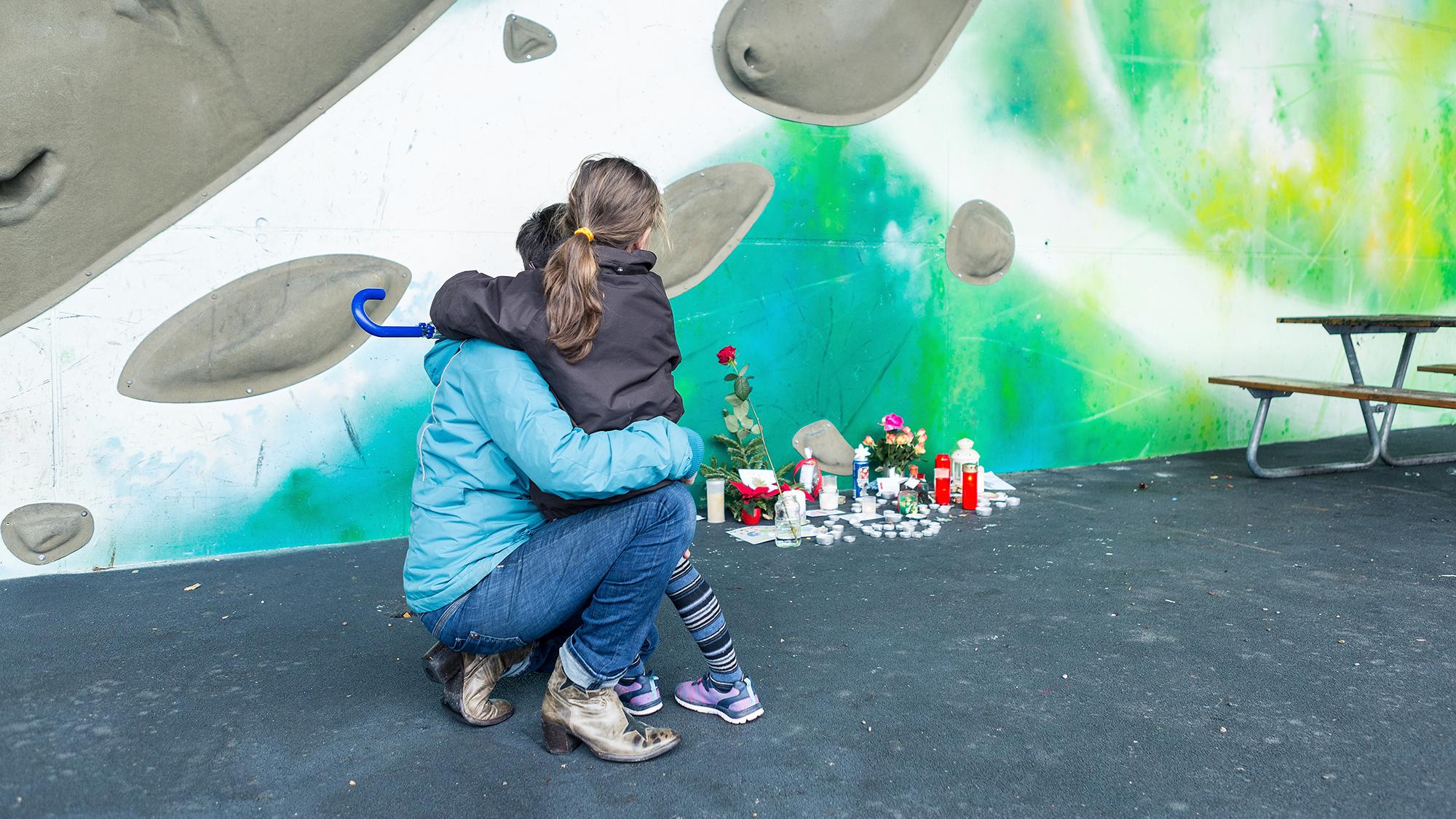 Warum ist Georges nicht mehr da? Eine Mutter trauert mit ihrem Kind am Gedenkort bei der Dreirosenbrücke.