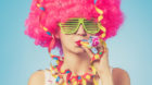 Portrait of beautiful woman in pink wig and green glasses. Close up