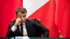 French President Emmanuel Macron touches his face during a joint press briefing with Chinese President Xi Jinping, not shown,