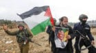 A Palestinian protester (C) holds a poster depicting former South African President Nelson Mandela during a demonstration aga