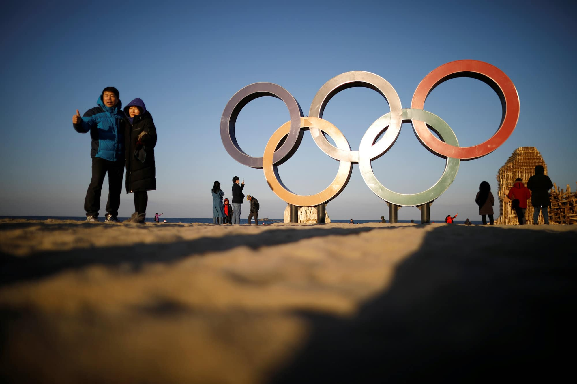 A couple poses for photographs next to the Olympic rings on a beach in Gangneung, South Korea February 3, 2018.  REUTERS/Kim