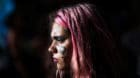 A woman has the symbol for women painted on her face during a demonstration on International Women's Day in Buenos Aires, Arg