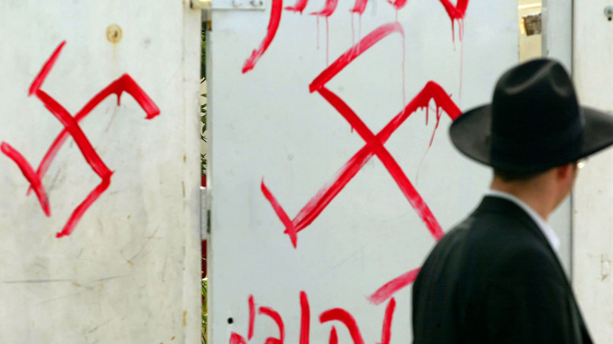 PETAH TIKVA, ISRAEL - MARCH 5:  (ISRAEL OUT)  A Jewish man looks at anti-semitic graffiti which was sprayed on the gate of a