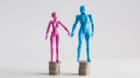 Male and female figurines holding hands looking at each other, standing on top of equal piles of coins. Income equality conce