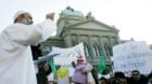 An unidentified Imam speaks in front of the house of parliament during a demonstration in Berne, February 11, 2006. The prote