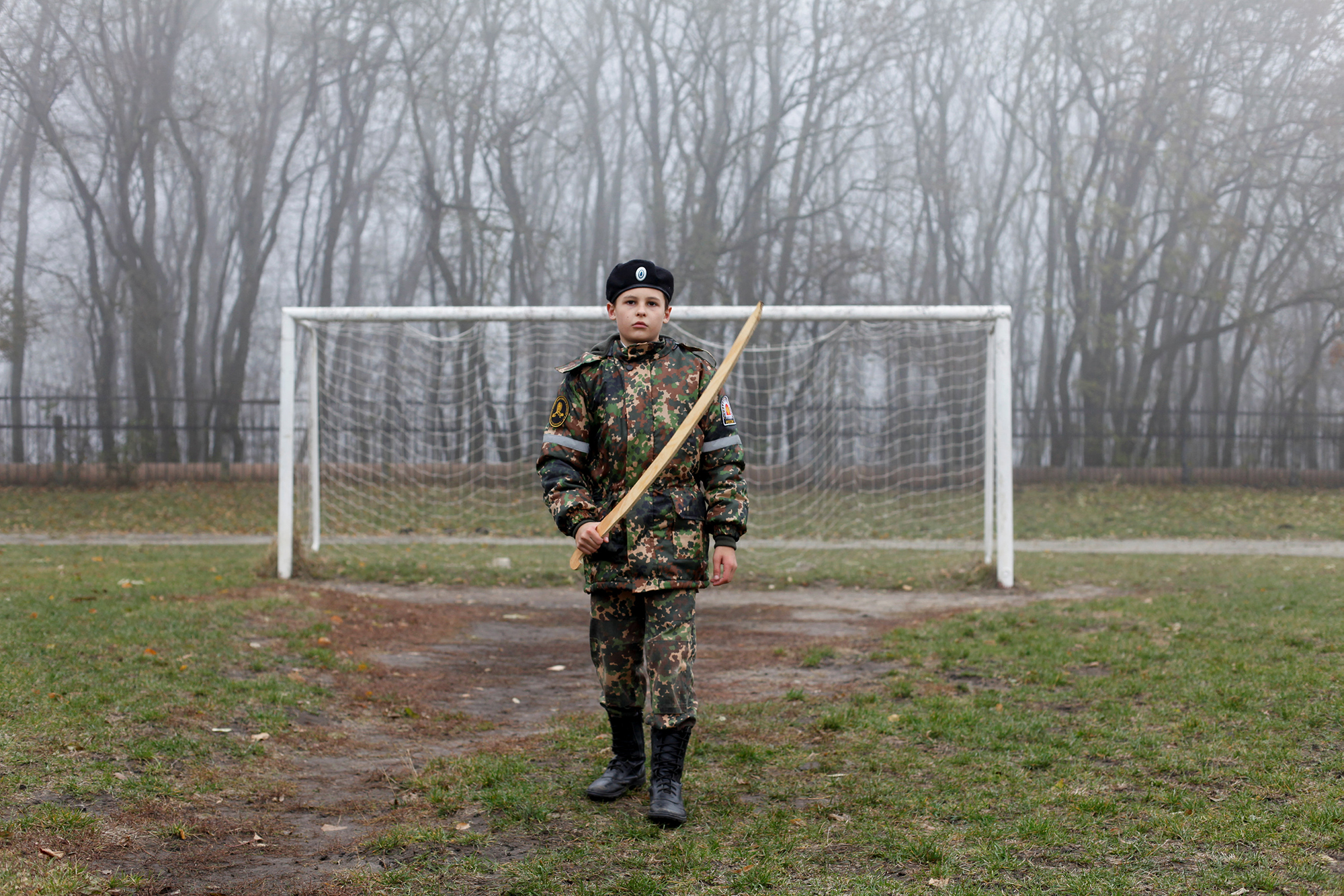 A cadet holds a model of a sword in front of a goalpost as he trains at the stadium of the General Yermolov Cadet School in S