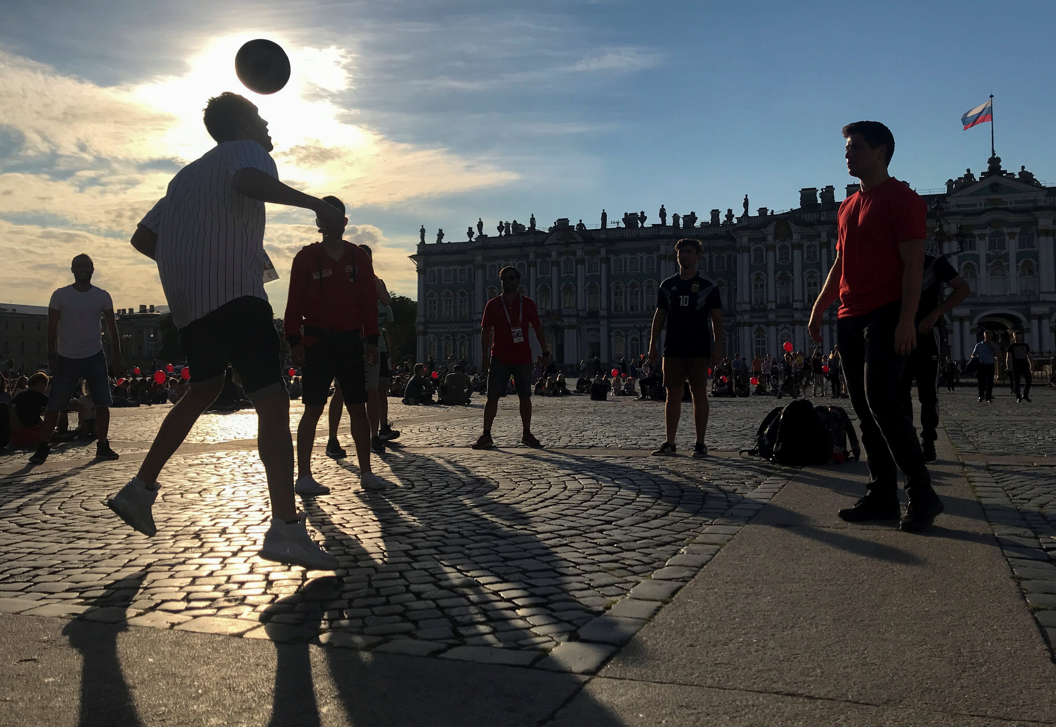 People play soccer at Palace Square with Hermitage Museum in the background in Saint Petersburg, Russia, July 11, 2018. As we