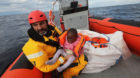 Oscar Camps, founder of Spanish NGO Proactiva Open Arms, holds a migrant child inside a rescue craft after pulling it from an