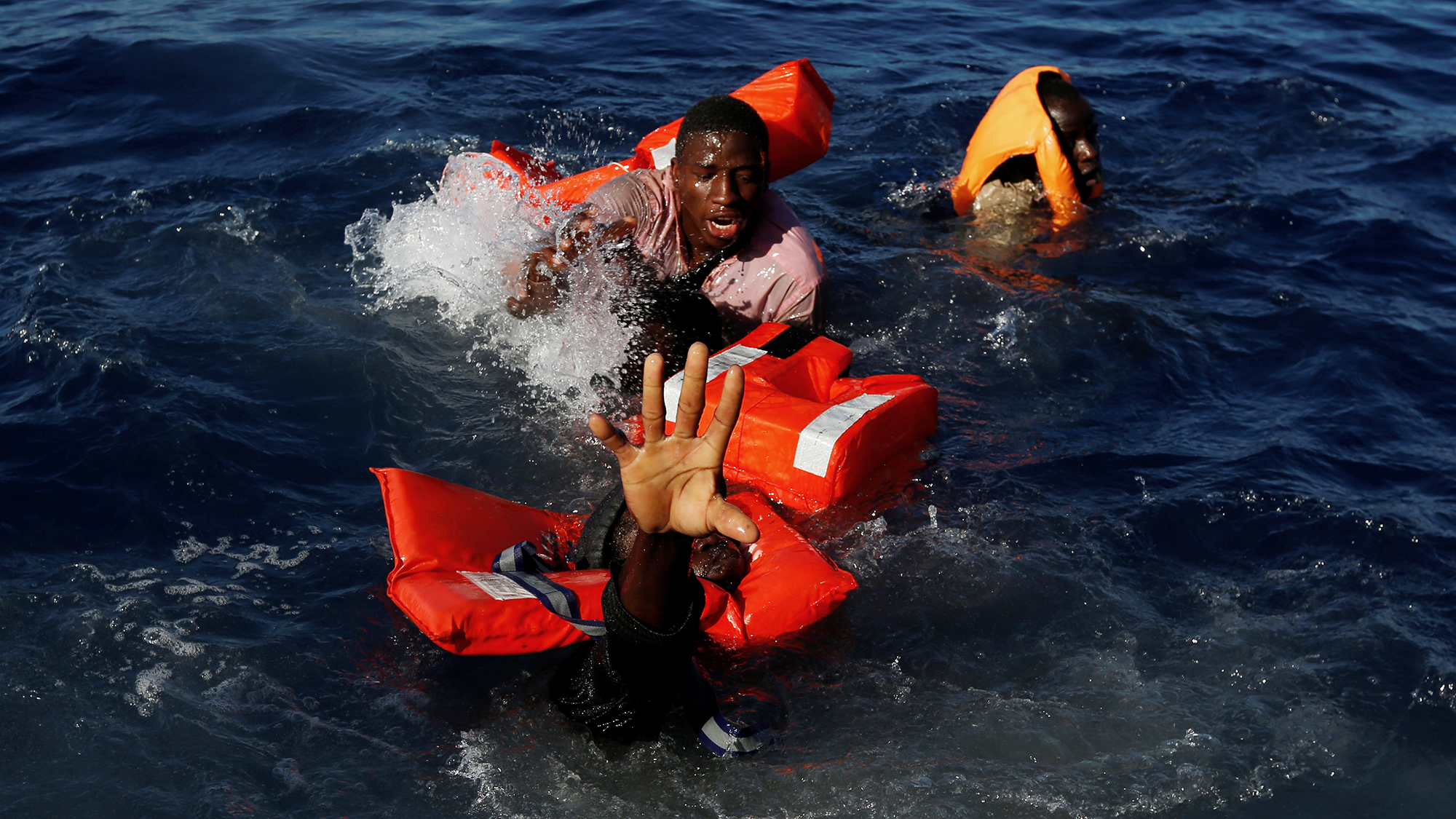 Migrants try to stay afloat after falling off their rubber dinghy during a rescue operation by the Malta-based NGO Migrant Of