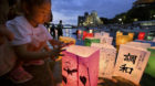 A girl releases paper lanterns on the Motoyasu river facing the gutted Atomic Bomb Dome in remembrance of atomic bomb victims