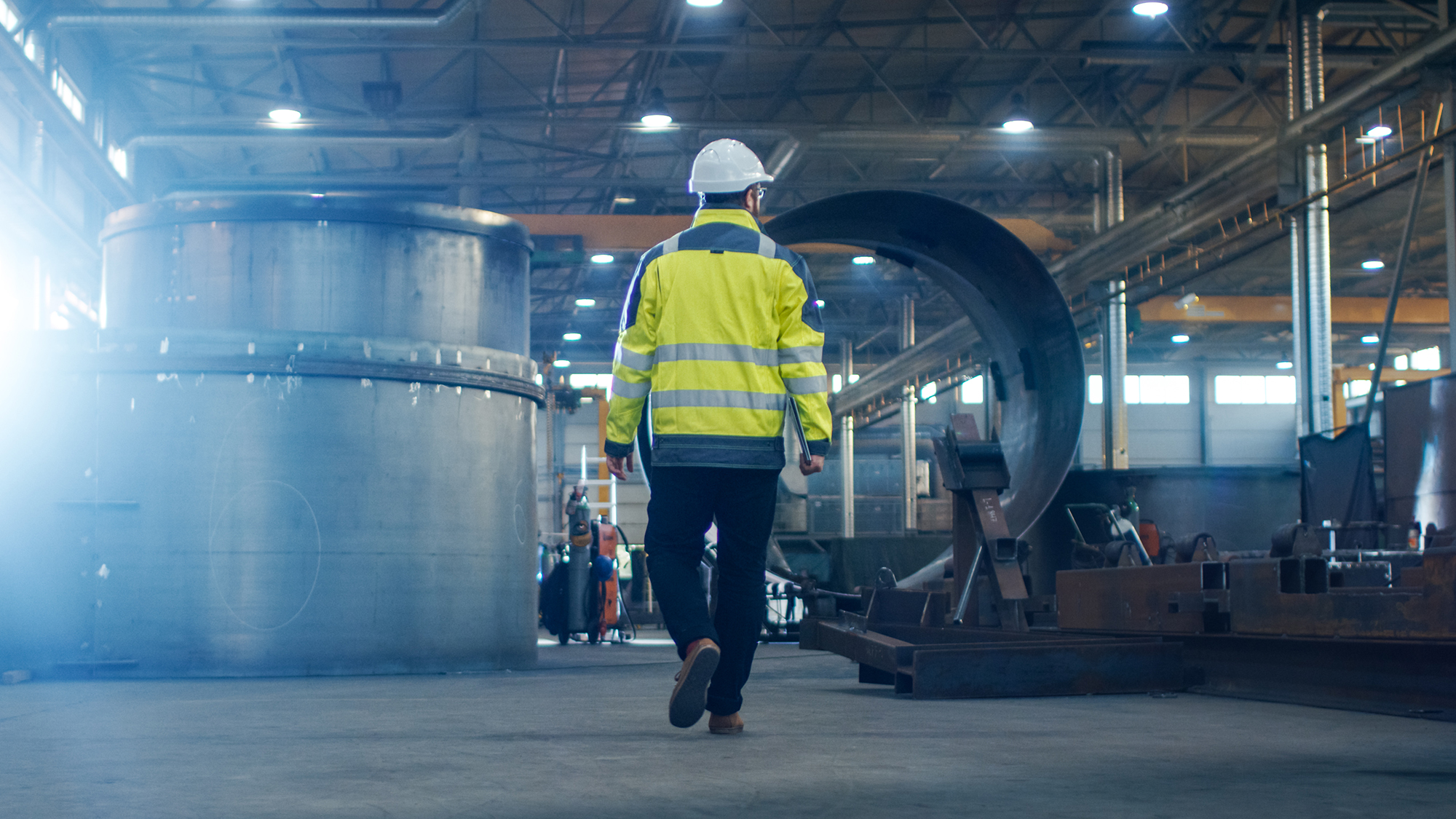 Industrial Engineer in Hard Hat Wearing Safety Jacket Walks Through Heavy Industry Manufacturing Factory with Various Metalwo