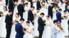 HANGZHOU, CHINA - APRIL 21: Newly-wed couples attend a group wedding ceremony before International Workers Day on April 21, 2