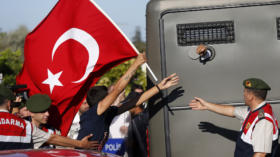 Protesters run after a prison van as an unidentified defendant sticks his fist out as he's driven to a courthouse in Silivri,