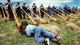 A young lover of the Alphorn kneels down to listen closely to the sound of the Alphorn on the Swiss mountain Maennlichen in t