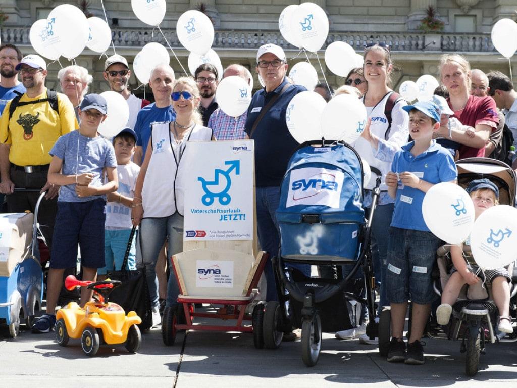 Aktivisten werben mit Kinderwagen und Ballonen für die Volksinitiative für einen vierwöchigen Vaterschaftsurlaub. (Archivb